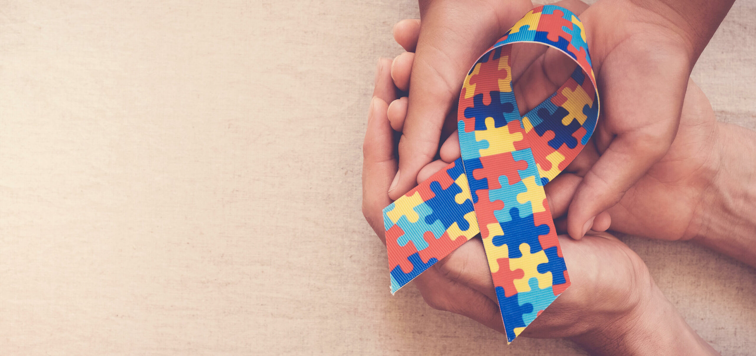 rsz hands holding puzzle ribbon autism awareness banner